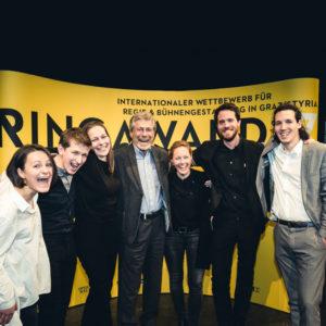 Die drei Teams für das Finale des RING AWARD zusammen mit Heinz Weyringer vor einer gelben Wand, Copyright Lupi Spuma