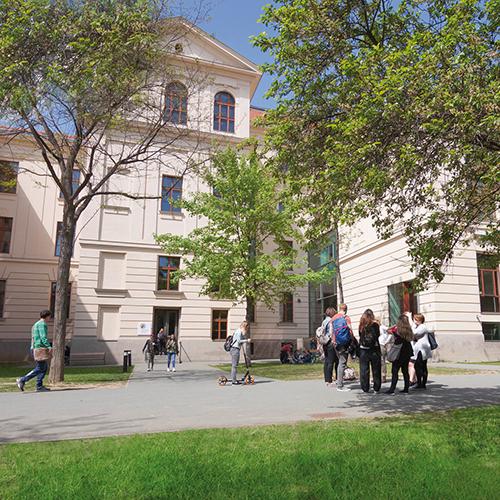 Innenhof der Pädagogischen Hochschule, Menschen sind darauf zu sehen, sie stehen in Gruppen und unterhalten sich, Wiesen und Bäume sind grün, die Fassade weiß